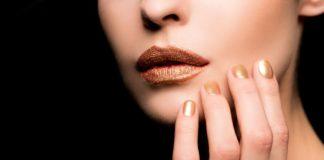 Frau mit gold lackierten Fingenägeln