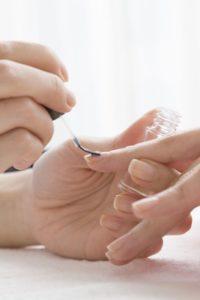 Frau trägt Nagelpföege auf